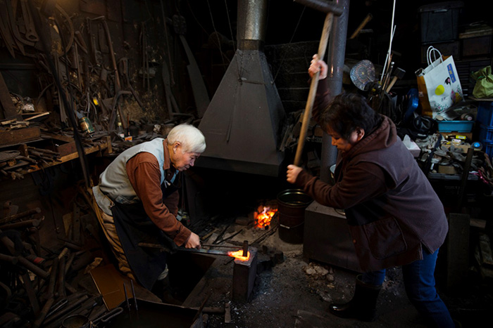 Helping each other, they produce a lacquer plane by hammering steel on iron. Anticipating each other's movements is still work on progress.